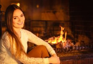 Smiling woman sitting beside fireplace
